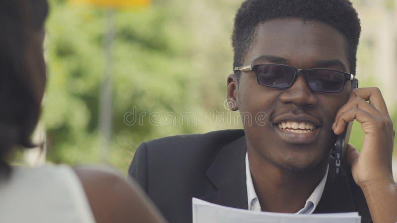 Empresario afroamericano positivo joven en las gafas de moda que tienen conversación telefónica con el donante auxiliar de la sec foto de archivo libre de regalías