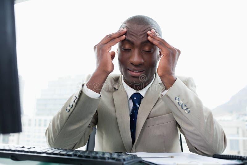 Empresario agotado que trabaja con un ordenador fotos de archivo