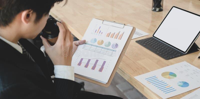 Empresario analizando la estrategia con gráficos y gráficos en el documento imagen de archivo