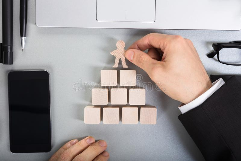 Empresario Arranging Human Figure cortado en bloques de madera foto de archivo