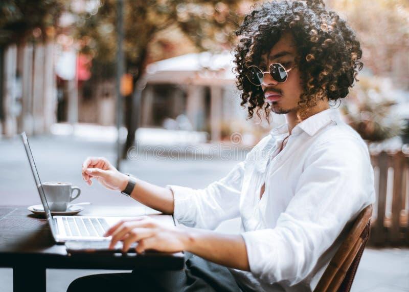 Empresario asiático del hombre con el ordenador portátil en un café al aire libre imágenes de archivo libres de regalías