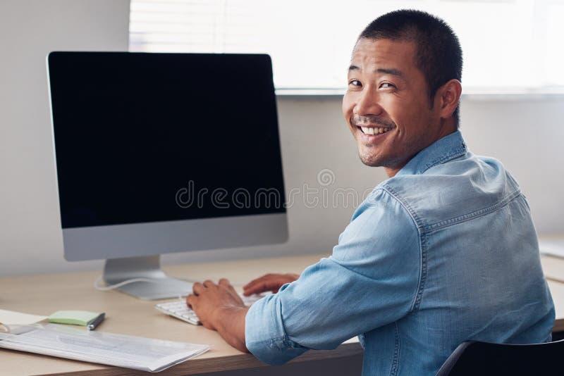 Empresario asiático joven feliz en el trabajo sobre un ordenador de oficina imagen de archivo
