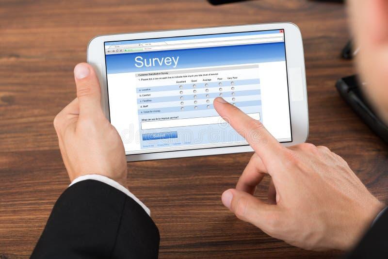 Empresario con la forma de la encuesta sobre la demostración del teléfono móvil imagenes de archivo