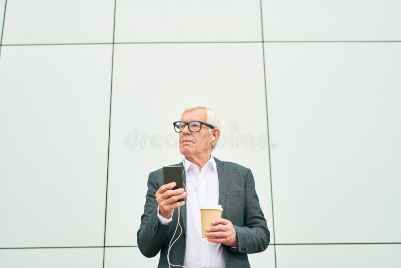 Empresario con la taza y smartphone que mira lejos imagen de archivo
