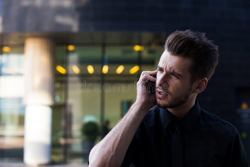 Empresario confiado de sexo masculino hermoso que llama vía el teléfono móvil, colocándose exterior imagen de archivo