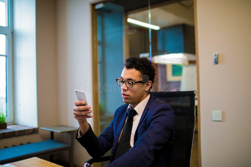 Empresario confiado de sexo masculino que charla en línea vía el teléfono móvil durante día del trabajo en empresa foto de archivo libre de regalías