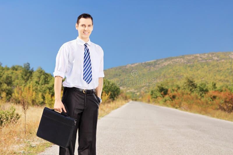 Empresario confiado joven que sostiene una maleta en un camino fotos de archivo libres de regalías