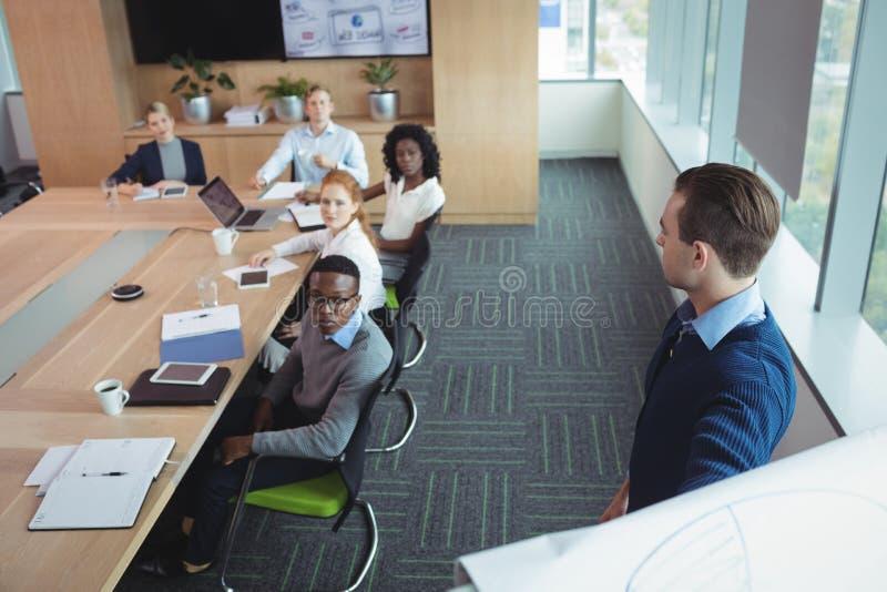 Empresario de negocio serio que explica estrategia a los colegas en la oficina fotos de archivo