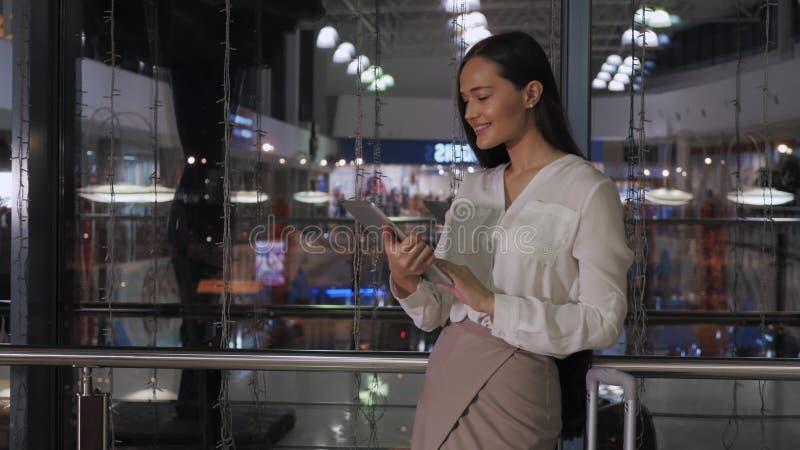 Empresario de sexo femenino joven que lee el libro electrónico en la tableta digital en la oficina moderna interior, empresaria e imagen de archivo libre de regalías