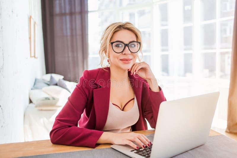 Empresario de sexo femenino joven que se sienta en la tabla en su Ministerio del Interior que trabaja en el ordenador port?til imágenes de archivo libres de regalías