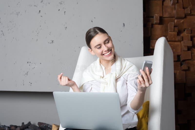 Empresario de sexo femenino sonriente que tiene llamada video en el teléfono móvil durante trabajo sobre el ordenador portátil fotografía de archivo libre de regalías