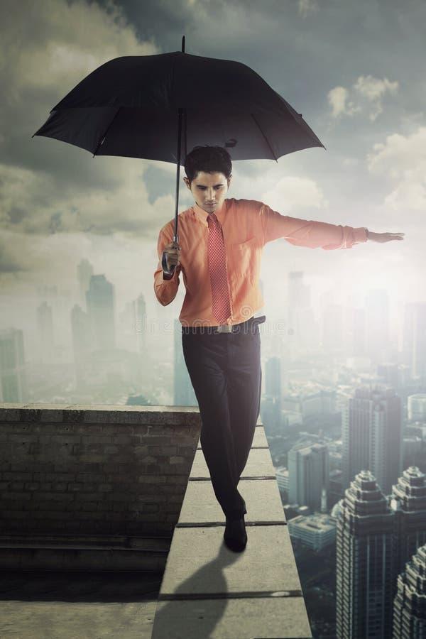 Empresario de sexo masculino con el paraguas en tejado imágenes de archivo libres de regalías