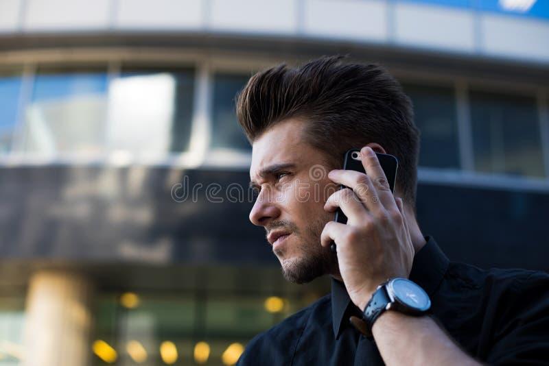 Empresario de sexo masculino confiado que llama vía el smartphone, colocándose exterior foto de archivo libre de regalías