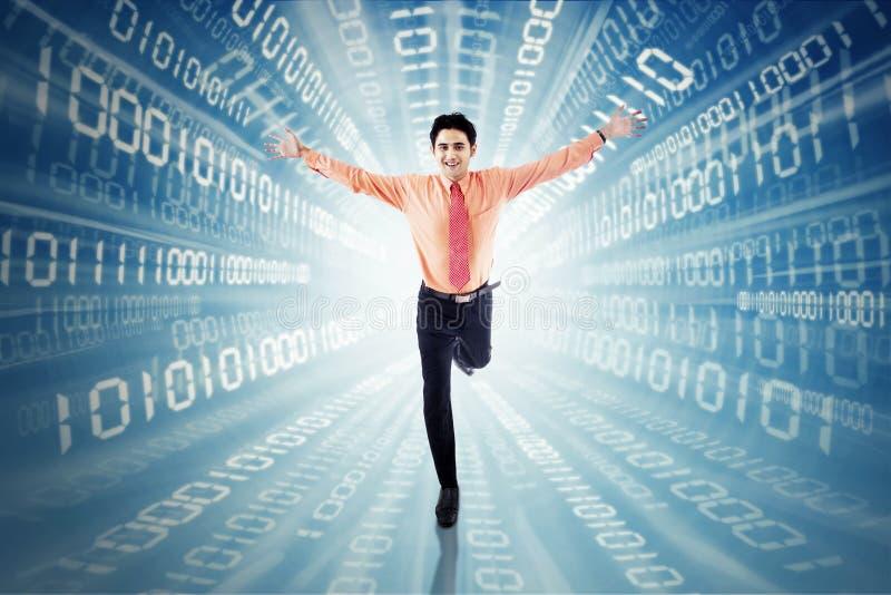 Empresario de sexo masculino que corre con código binario imagen de archivo libre de regalías