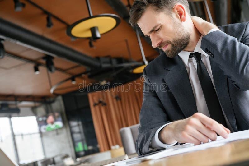 Empresario en almuerzo de negocios en el restaurante que se sienta tocando el dolor muscular del cuello foto de archivo