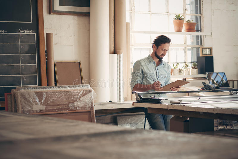 Empresario en su taller que comprueba figuras en un tablero fotos de archivo