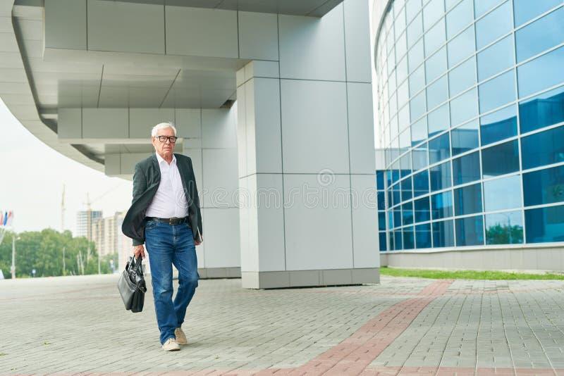 Empresario envejecido que camina para trabajar foto de archivo libre de regalías