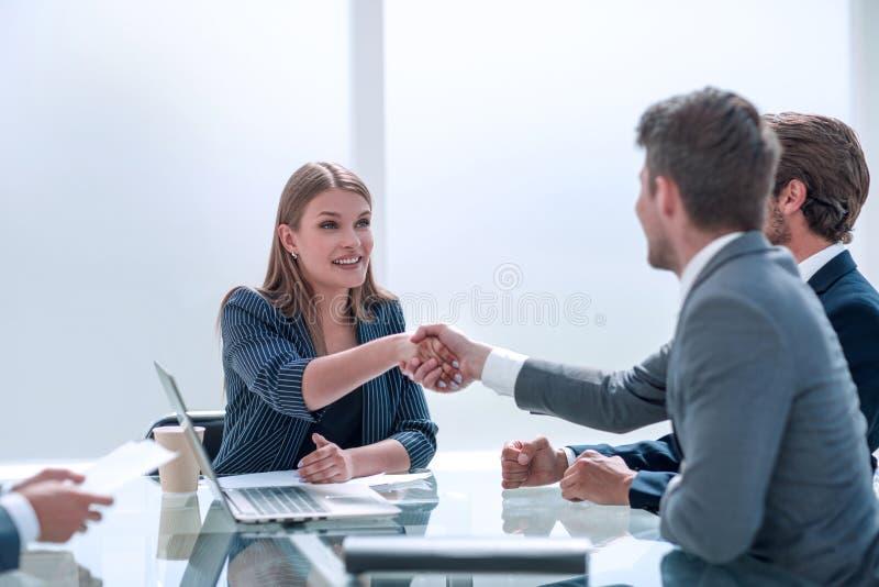 Empresario estrechando la mano con una mujer de negocios sentada en la mesa de negociación fotografía de archivo