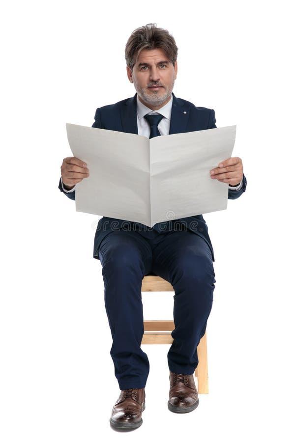 Empresario formal sentado con el periódico en las manos mirando la cámara foto de archivo libre de regalías