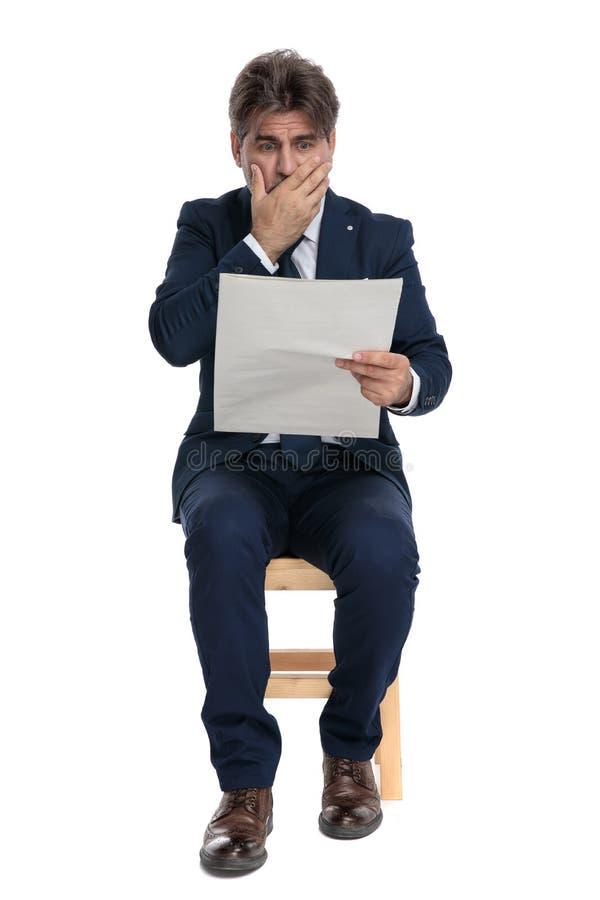 Empresario formal sentado leyendo el periódico aterrorizado fotografía de archivo