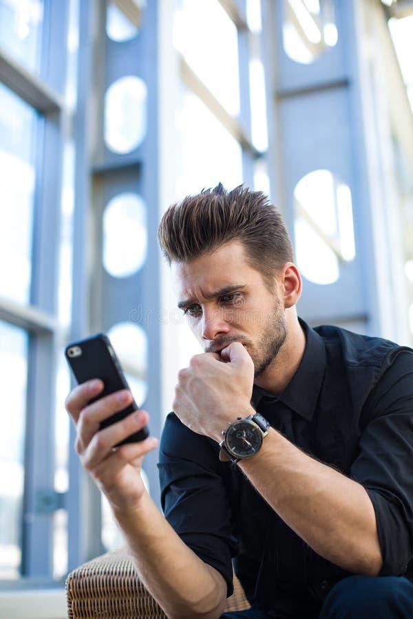 Empresario frustrado que tiene problema, leyendo vía voto negativo móvil sobre su proyecto fotos de archivo