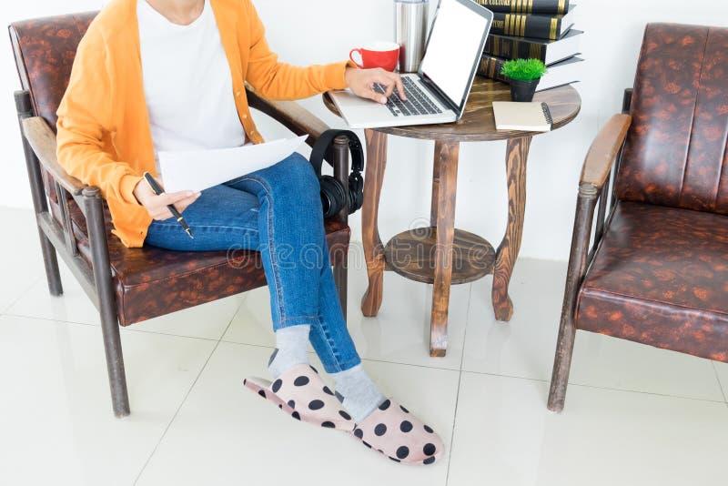 Empresario hermoso joven atractivo Woman que sonr?e y que mira la pantalla del ordenador port?til, trabajando de hogar foto de archivo libre de regalías