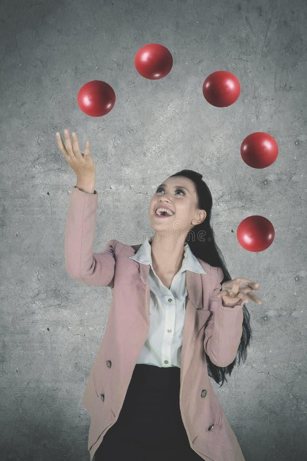 Empresario hermoso que hace juegos malabares bolas rojas fotos de archivo libres de regalías