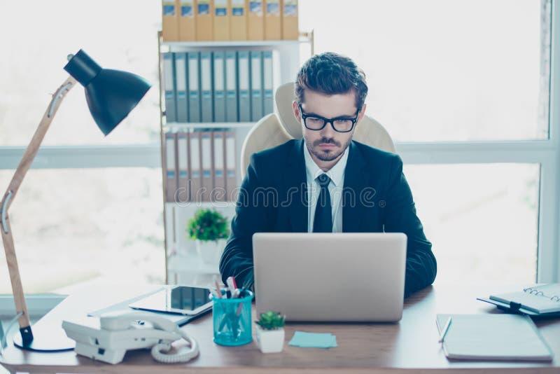 Empresario importado acertado joven con el lazo que trabaja con lapto imagen de archivo libre de regalías