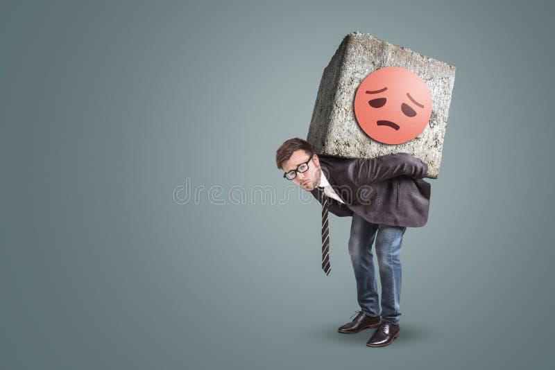 Empresario infeliz que dobla debajo de una piedra grande en el suyo detrás imagen de archivo