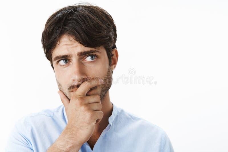 Empresario joven en cuestión pensativo con los ojos azules profundos y erizarse llevando a cabo la mano en el mandíbula que mira  fotos de archivo