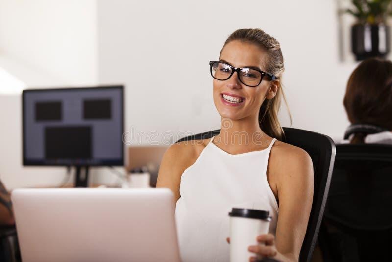 Empresario joven que sonríe en su oficina de lanzamiento foto de archivo