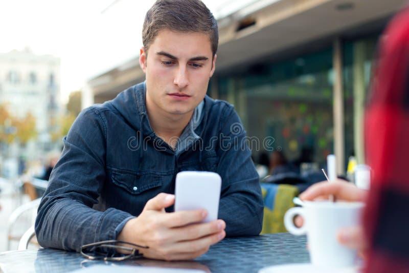 Empresario joven que usa su teléfono móvil en la cafetería imagen de archivo libre de regalías