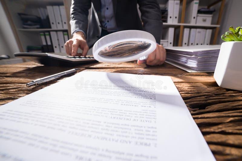 Empresario Looking At Document con la lupa imagenes de archivo