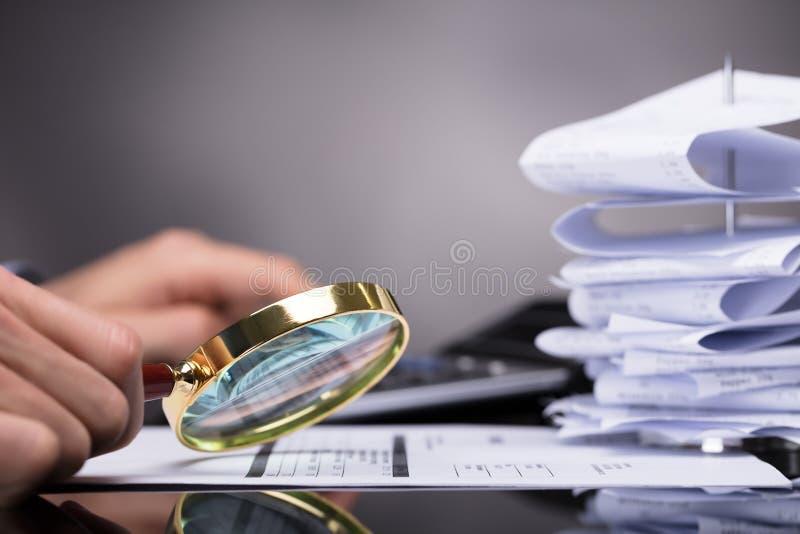 Empresario Looking At Invoice a través de la lupa imagenes de archivo