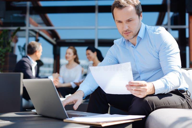 Empresario profesional apuesto que estudia el documento foto de archivo libre de regalías