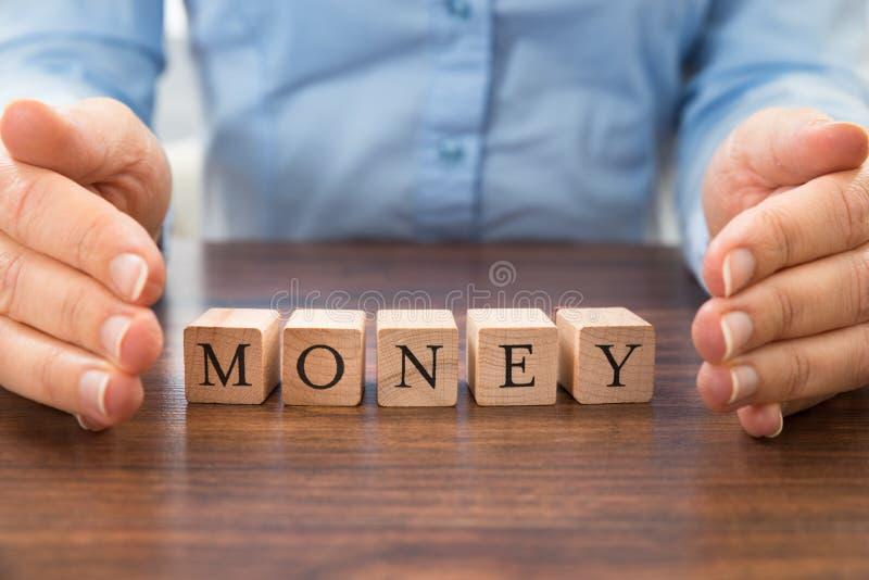 Empresario que ahorra el dinero de la palabra imagen de archivo