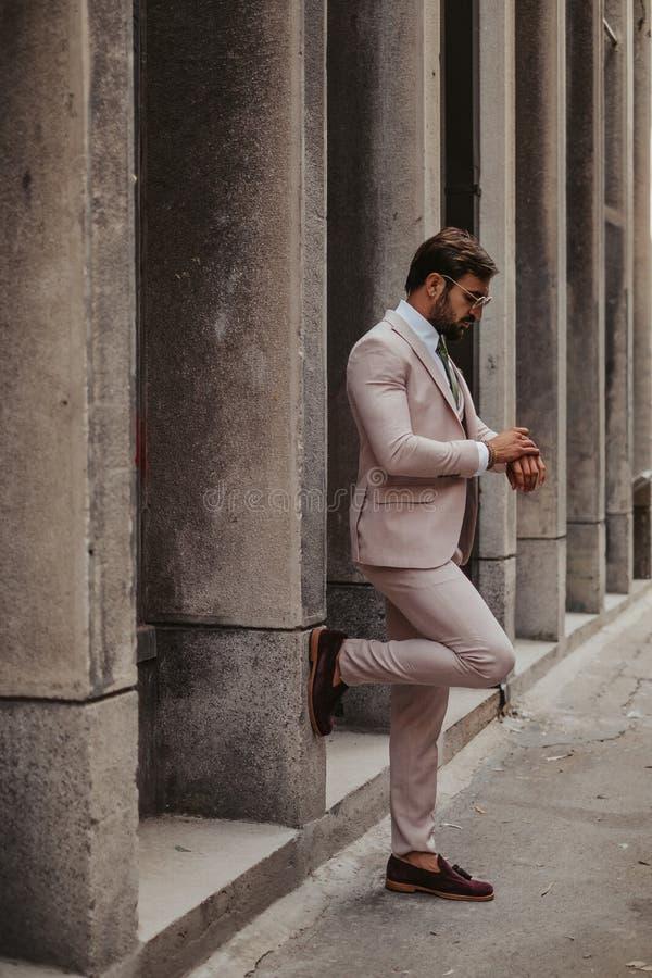 Empresario que mira su reloj mientras que espera imagen de archivo