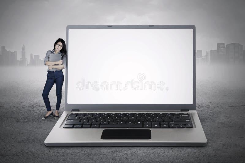 Empresario que se coloca con el ordenador portátil grande fotografía de archivo