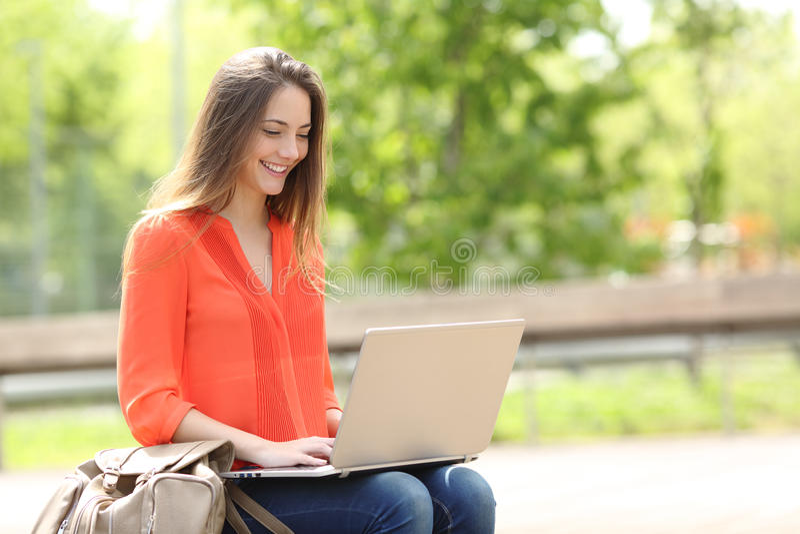 Empresario que trabaja con un ordenador portátil en un parque fotografía de archivo libre de regalías