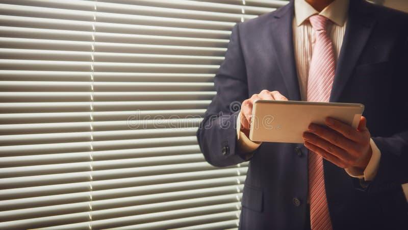 Empresario que trabaja en la tableta digital foto de archivo
