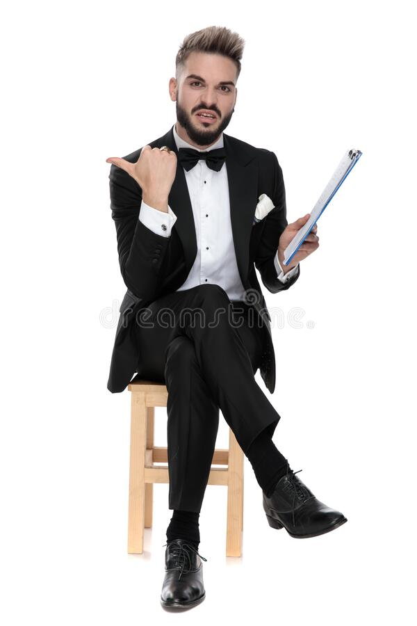 Empresario sentado y sosteniendo el portapapeles mientras apuntaba a un lado disgustado fotos de archivo libres de regalías
