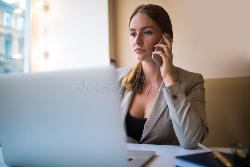 Empresario serio de la mujer que tiene conversación del teléfono móvil durante webinar imágenes de archivo libres de regalías