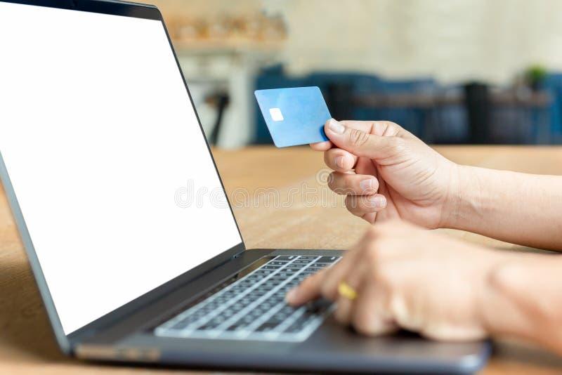Empresario sosteniendo una tarjeta de crédito y usando una laptop en una mesa de madera imagen de archivo