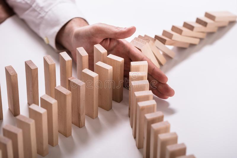 Empresario Stopping Wooden Blocks de caer imagen de archivo libre de regalías