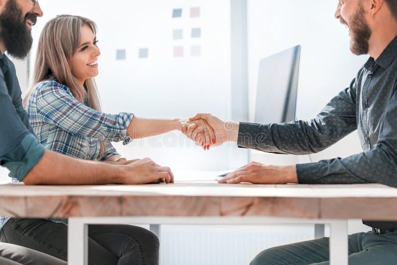 Empresario y empresaria dándole la mano durante una reunión de trabajo foto de archivo