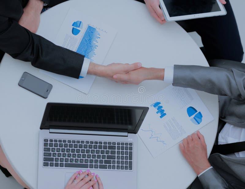 Empresarios acertados que sacuden las manos en una oficina moderna imagen de archivo