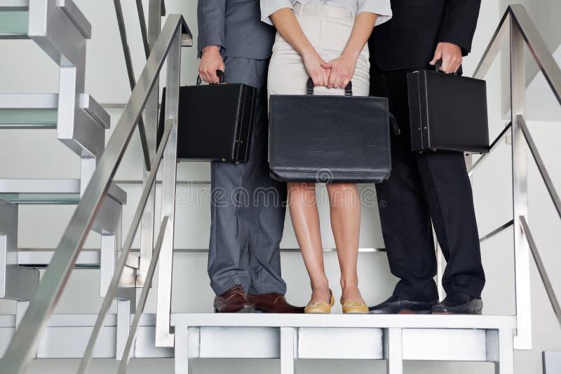 Empresarios con las carteras que se colocan en pasos imagen de archivo libre de regalías