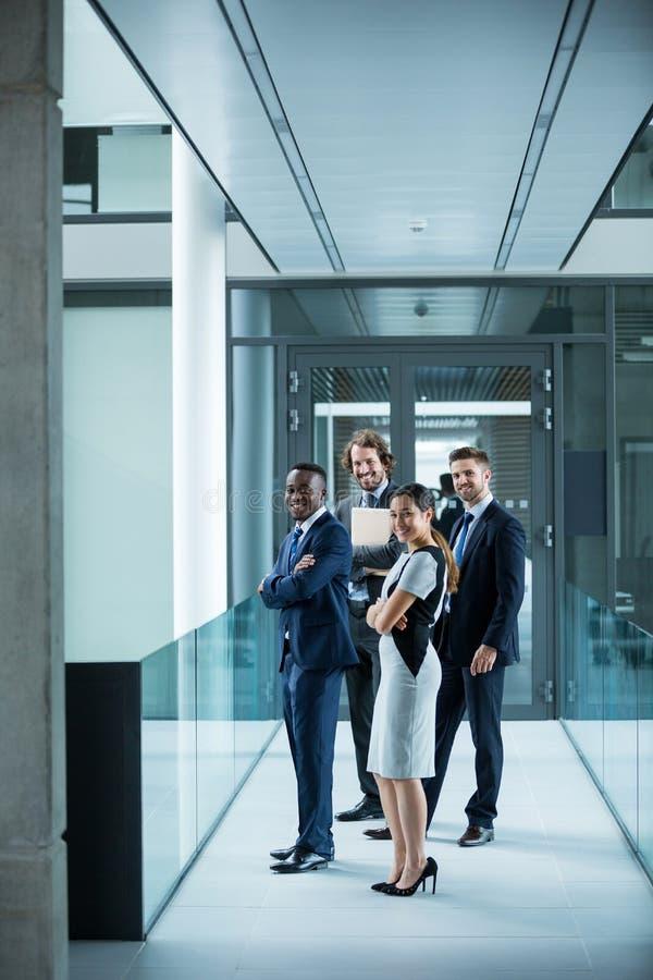 Empresarios confiados que se colocan en oficina foto de archivo libre de regalías