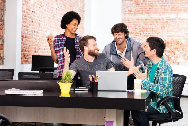 Empresarios diversos del grupo de raza de la mezcla de la oficina de la gente que ríen la discusión fotografía de archivo