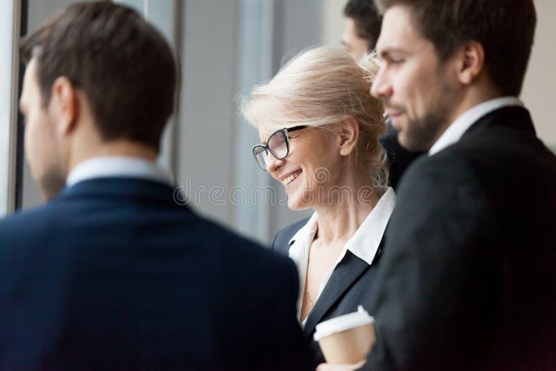 Empresarios ejecutivos felices que miran con planes de futuro del edificio de la ventana de la oficina imagenes de archivo